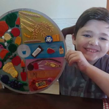 Uno de los niños muestra orgulloso su trabajo sobre alimentación  saludable  hecho en porcelana fría.